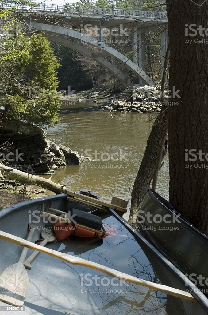 Water-filled Canoe at the side of a river stock photo