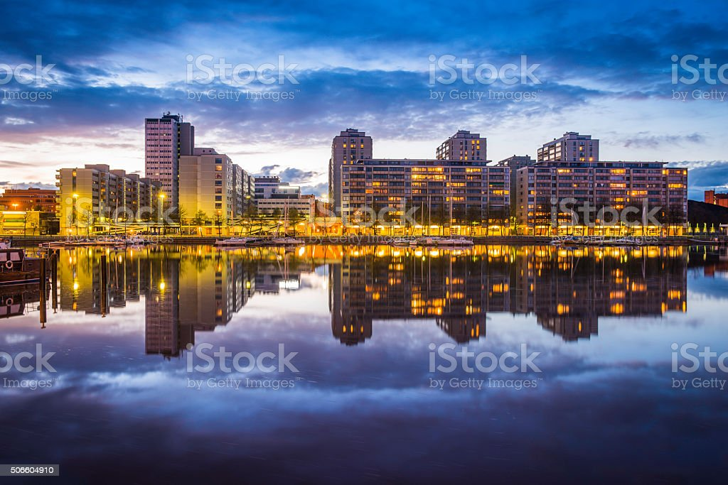 Waterfront apartments reflecting in yacht marina harbour at sunset Helsinki stock photo