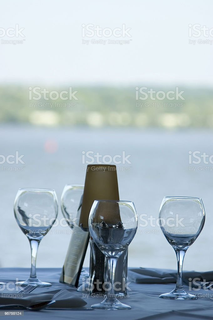 Waterfront dining with wine glasses royalty-free stock photo