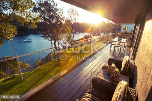 Waterfront house balcony at sunset