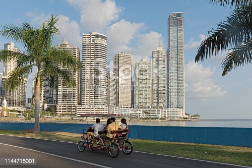 panama city, panama - march 25, 2019: four cyclists on the waterfront in front of the skyline