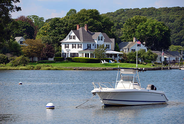 Waterfront luxury house Luxury house on the water's edge - boat and trees. riverbank stock pictures, royalty-free photos & images