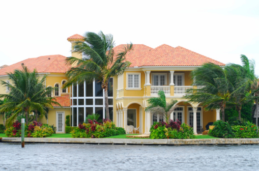 Waterfront mansion with palm trees