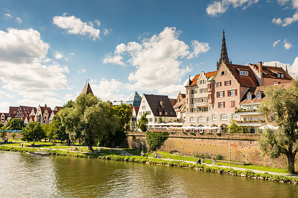 Waterfront of Ulm Ulm, Germany - August 13, 2016: People walking along the Danube river in Ulm, Germany on August 13, 2016. Ulm has the highest spire of the world. Foto taken from Donaustrasse. ulm stock pictures, royalty-free photos & images