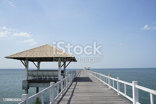Waterfront pavilion against on blue sky,white wooden bridge stretching to clear sea in sunshine day.Feeling freedom vacation time in Thailand.