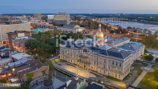 The capital statehouse of New Jersey lights up as the sun sets the Delaware River in the background city of Trenton