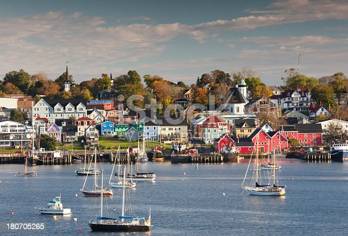 The beautiful and historic town of Lunenburg, Nova Scotia in the fall. Boats drift in the harbour and the amazing colours of the buildings in this picturesque seaside town add to the scene. This image was taken across the harbour from town on a gorgeous fall morning. Lunenburg is located approximately an hour from Halifax.