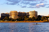 Washington, DC, USA - June 07 2016: Watergate hotel and apartments at golden hour with a Kayak in the Potomac.