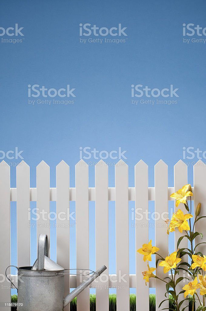 Watering Can And Flowers With White Fence royalty-free stock photo