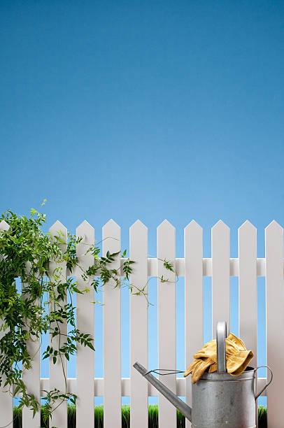 gießkanne und handschuhe mit weißen zaun - lattenzaun garten stock-fotos und bilder