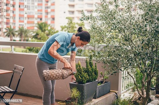 Young woman watering plants at home garden on the balcony