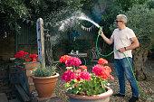 Man with hose in courtyard garden