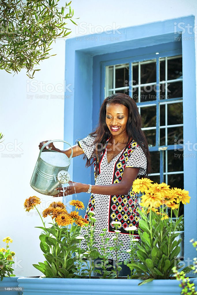 Watering the flowers Happy african woman watering the flowers in front of her house. Activity Stock Photo