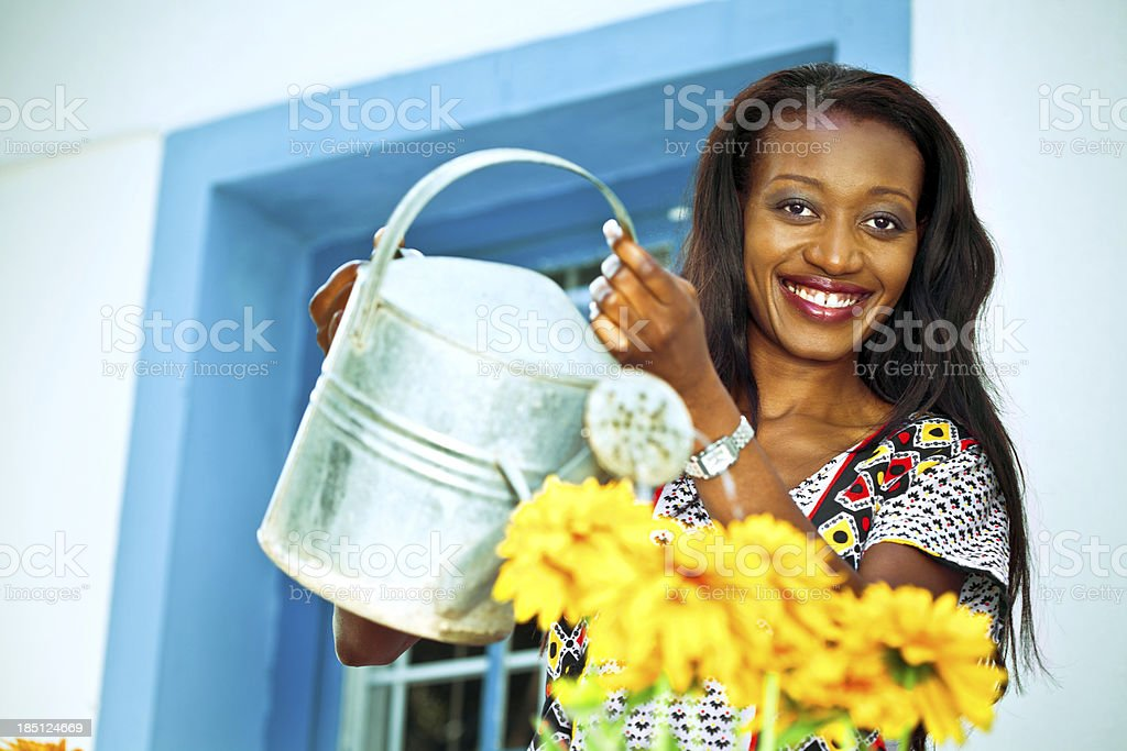 Watering the flowers Happy african woman watering the flowers in front of her house, smiling at the camera. Activity Stock Photo