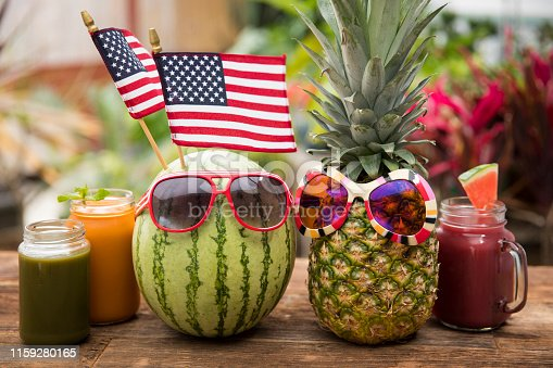 This is a photograph of a watermelon and pineapple with sunglasses sitting on a wooden picnic bench symbolizing summertime fun, tropical food and healthy eating