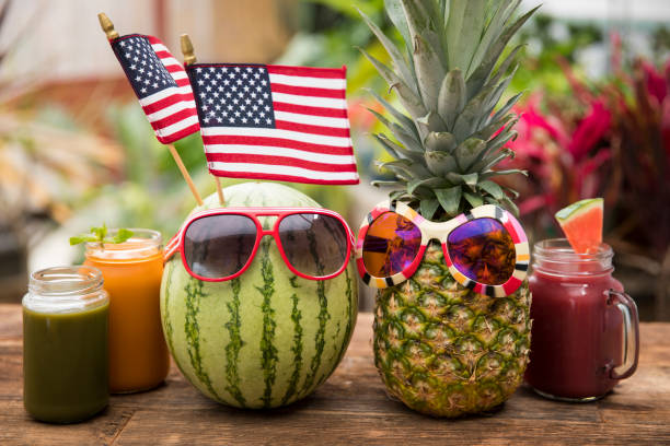 Watermelon and pineapple with sunglasses on picnic bench stock photo