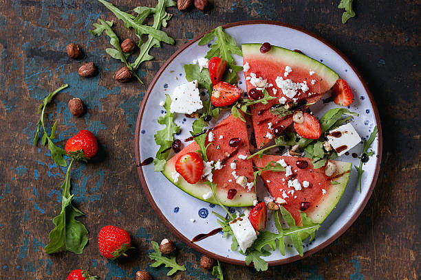 Watermelon and strawberry salad Blue spotted plate with watermelon and strawberry fruit salad with feta cheese, arugula, nuts and balsamic sauce, served over old dark wood background. Top view. Healthy eating concept balsamic vinegar stock pictures, royalty-free photos & images