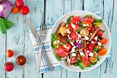 Watermelon and mixed tomato salad with feta cheese, overhead scene on rustic blue wood