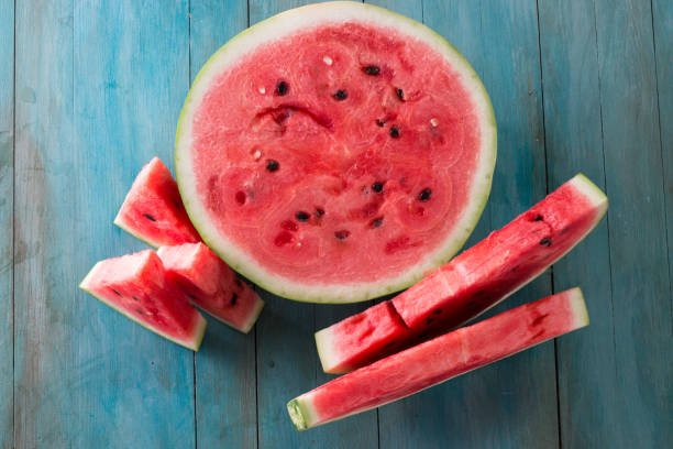 watermelon and watermelon pieces in a wooden background. stock photo