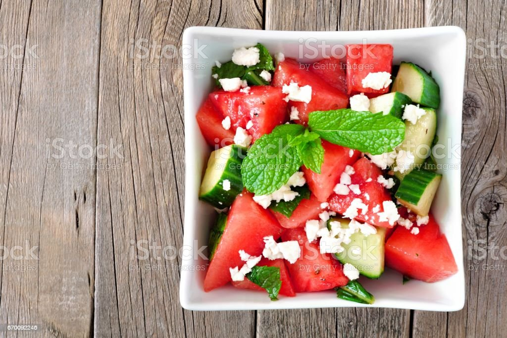 Watermelon, cucumber and feta cheese salad on a wood background stock photo