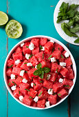 A watermelon feta and mint said with lime juice and olive oil on a vibrant aqua colored picnic table.   Please see my portfolio for other food and drink images.
