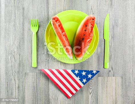 470765518 istock photo Watermelon In Plastic Plate On Wooden Table With American Flag 519729552