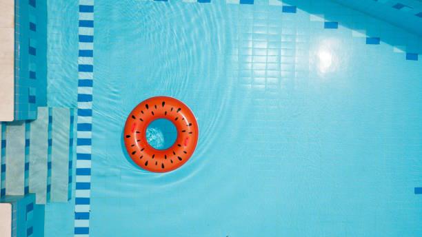 vattenmelon uppblåsbar ring flytande i pool - flotte bildbanksfoton och bilder