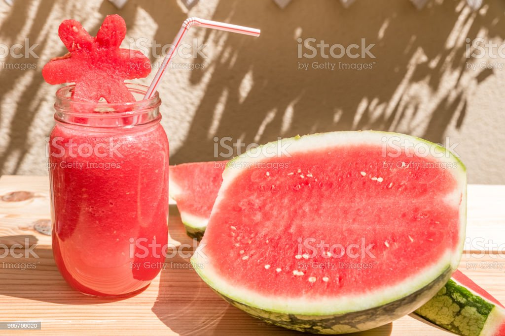 watermelon juice in glass cup with straw and slice of watermelon on wooden table with mediterranean garden background - Royalty-free Agriculture Stock Photo