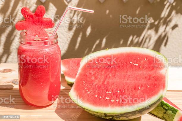 Watermelon Juice In Glass Cup With Straw And Slice Of Watermelon On Wooden Table With Mediterranean Garden Background - Fotografias de stock e mais imagens de Agricultura
