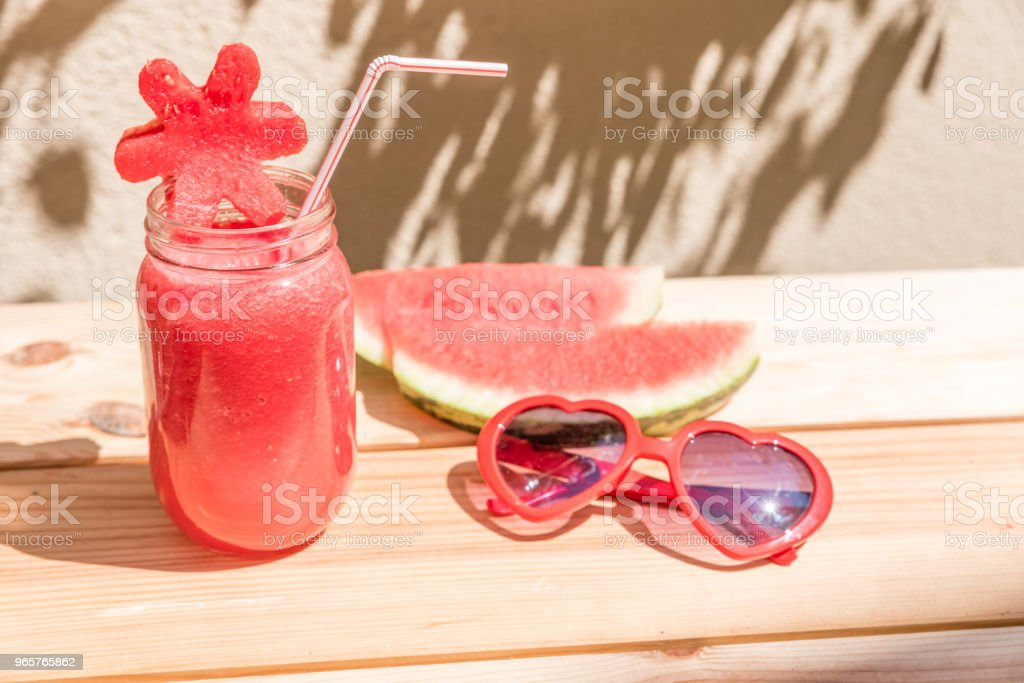 watermelon juice in glass cup with straw, slices of watermelon and red sunglasses with heart shape on wooden table with mediterranean garden background - Royalty-free Agricultura Foto de stock