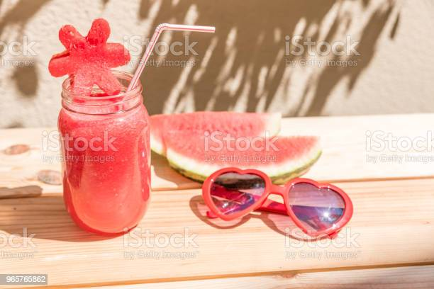 Watermelon Juice In Glass Cup With Straw Slices Of Watermelon And Red Sunglasses With Heart Shape On Wooden Table With Mediterranean Garden Background - Fotografias de stock e mais imagens de Agricultura