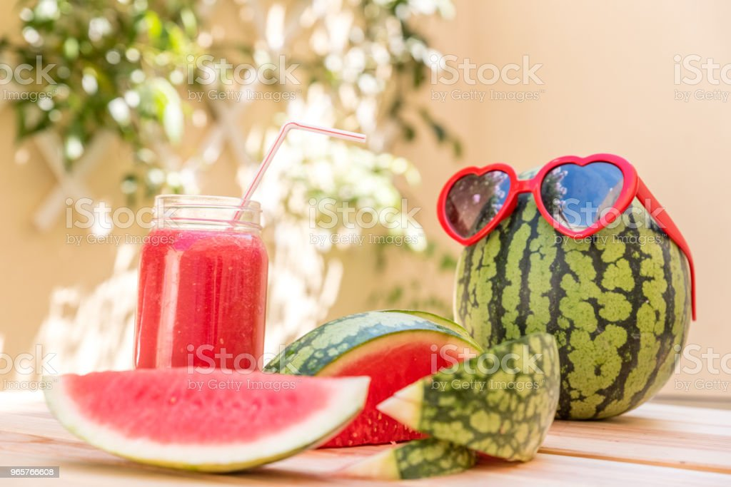 watermelon juice in glass cup with straw, watermelon slices and red heart-shaped glasses on wooden table with mediterranean garden background - Royalty-free Agriculture Stock Photo