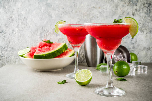 Watermelon margarita cocktail Watermelon margarita cocktail with lime and sliced watermelon, light concrete background copy space margarita stock pictures, royalty-free photos & images