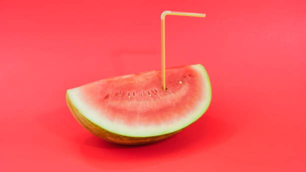 Watermelon on a red background with a straw stock photo