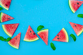 istock Watermelon pattern. Red watermelon on blue background. Summer concept. Flat lay, top view, copy space 1253894047