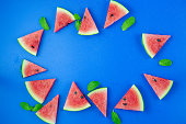 istock Watermelon pattern. Red watermelon on blue background. Summer concept. Flat lay, top view, copy space 1253894149