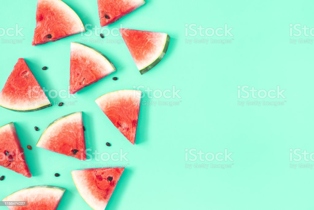 Watermelon pattern. Red watermelon on mint background. Summer concept. Flat lay, top view, copy space Watermelon pattern. Red watermelon on mint background. Summer concept. Flat lay, top view, copy space Above Stock Photo