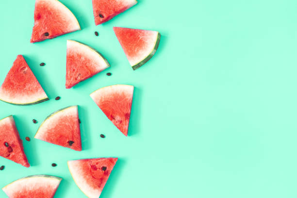 Watermelon pattern. Red watermelon on mint background. Summer concept. Flat lay, top view, copy space stock photo