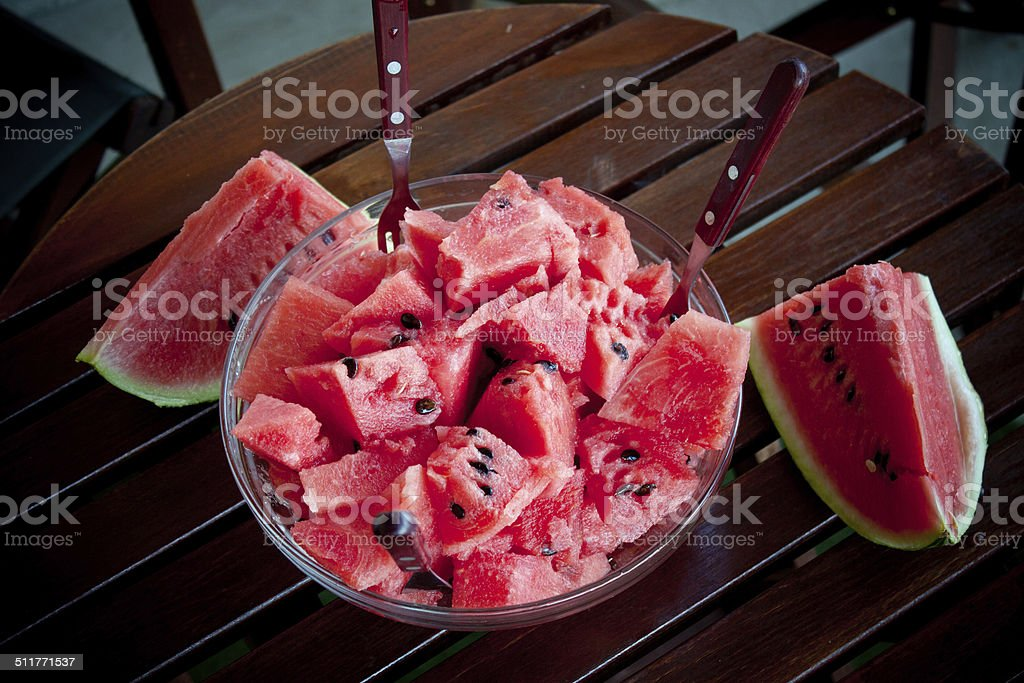 Watermelon picies in transparent bowl on wooden table stock photo
