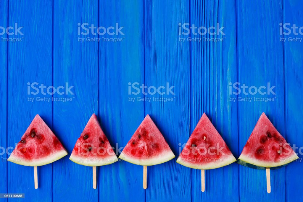 Watermelon popslices ornament on blue wooden background, free sp stock photo