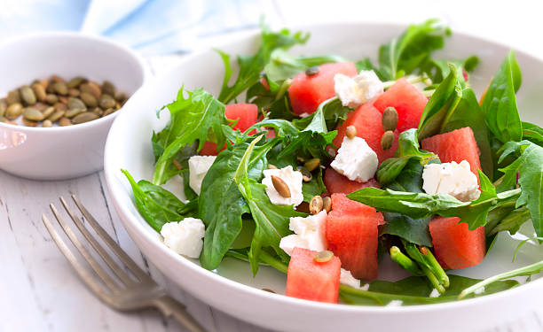 Watermelon Salad Watermelon salad with feta cheese, toasted pumpkin seeds, arugula, spinach and mint. feta cheese stock pictures, royalty-free photos & images