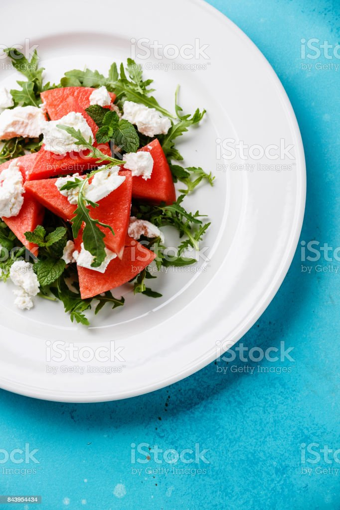 Watermelon salad with arugula, ricotta cheese and mint stock photo