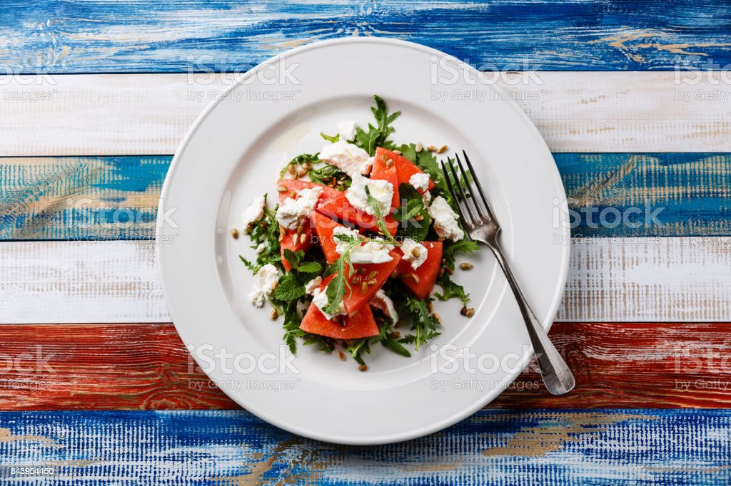 Watermelon salad with arugula, ricotta cheese and sunflower seed stock photo