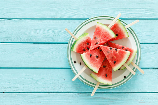 A young woman enjoying in juicy watermelon in her kitchen. Healthy eating. Enjoying food.