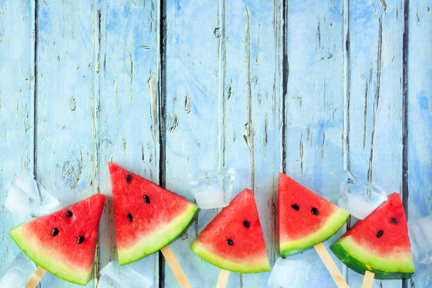 Watermelon slice popsicles bottom border against blue wood stock photo