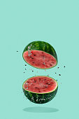 Watermelon sliced flying on pastel green background. Minimal fruit and summer concept.
