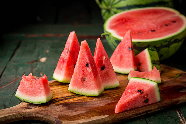 watermelon sliced on wood background - karpuz stok fotoğraflar ve resimler