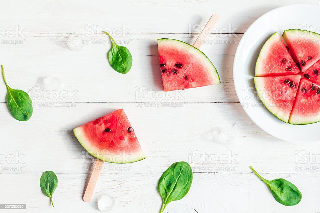 watermelon slices on sticks, spinach leaves and blueberries stock photo