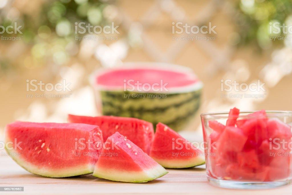 Watermeloen slices op houten tafel en glas cup met stukjes watermeloen, mediterrane tuin achtergrond - Royalty-free Bes Stockfoto
