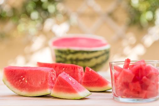 Watermeloen Slices Op Houten Tafel En Glas Cup Met Stukjes Watermeloen Mediterrane Tuin Achtergrond Stockfoto en meer beelden van Bes